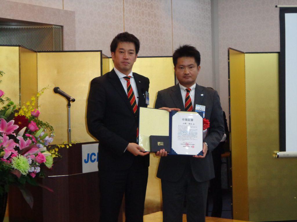 卒業証書と記念品を受け取る山岡委員